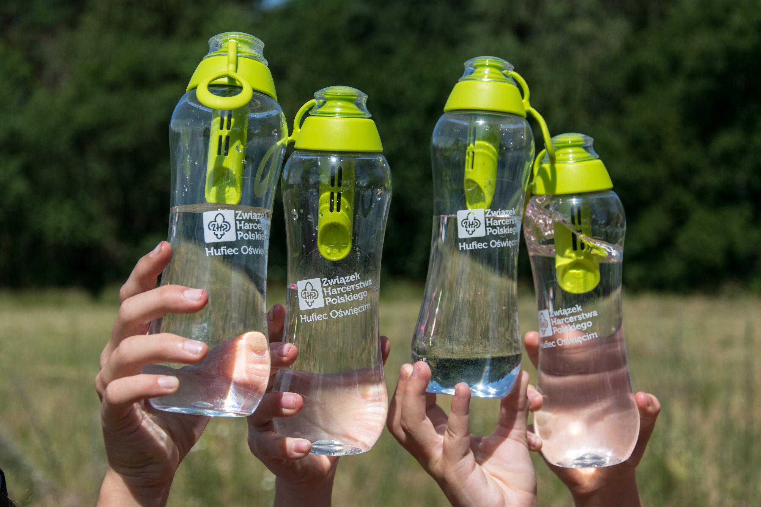 Wielorazowe butelki filtrujące wodę z naklejonym logo Hufca ZHP Oświęcim.